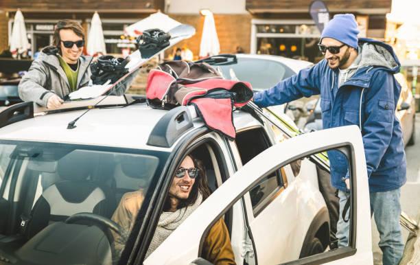 Trois jeunes hommes en tenue de ski qui montent dans une voiture