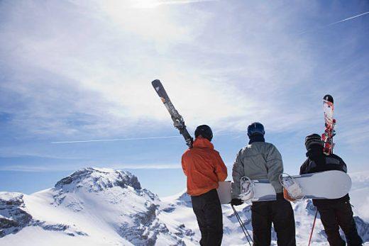 Trois personnes de dos, en tenue de ski, au sommet d'une montagne