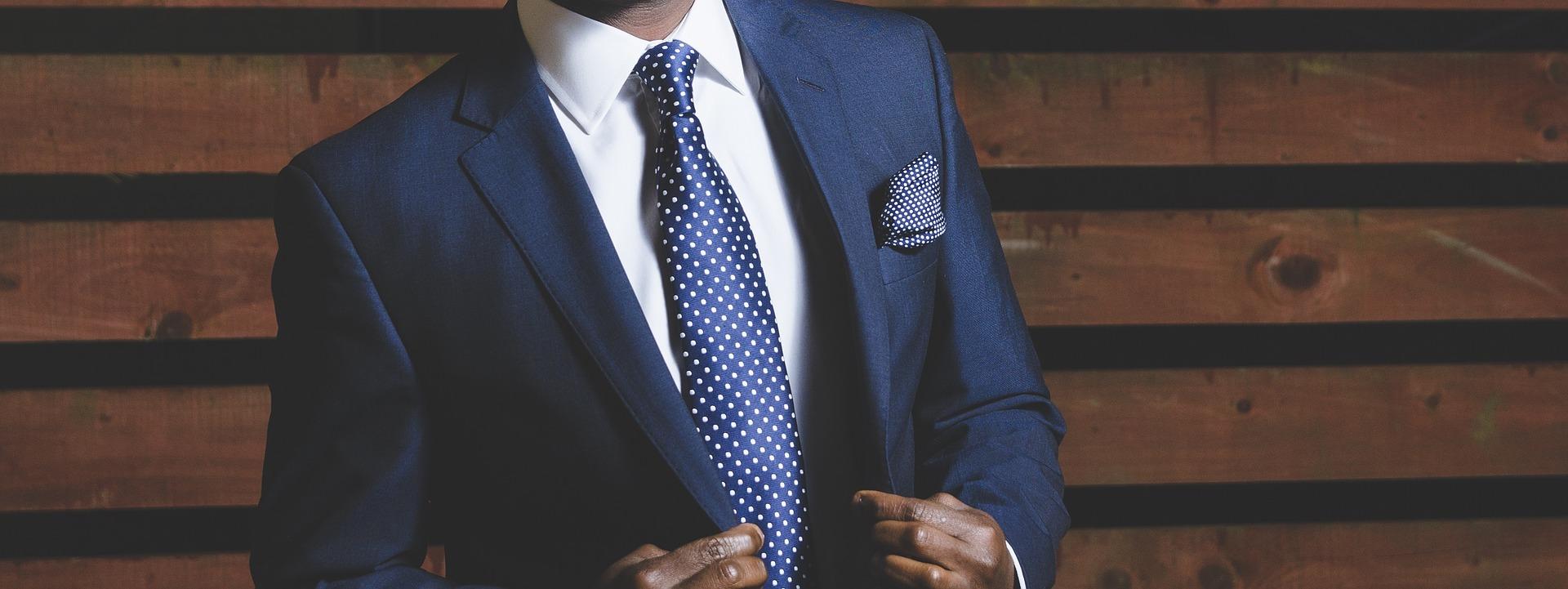 homme portant un costume bleu marine et une chemise blanche