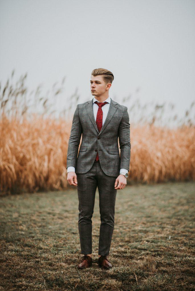 Jeune homme habillé en costume gris, chemise blanche et cravate rouge