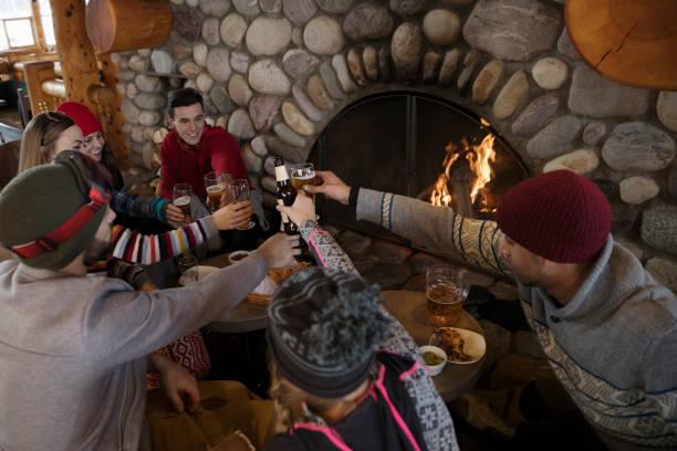 Un groupe d'amis qui trinquent devant un feu de bois dans une auberge