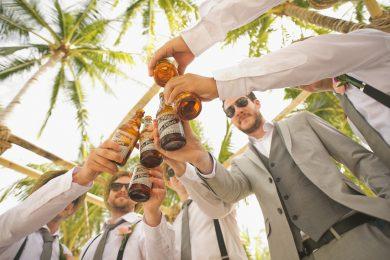 Groupe d'hommes en costumes et lunettes de soleil qui trinquent avec des bouteilles de bière