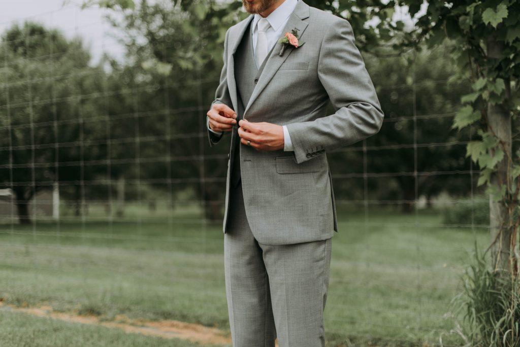 Gros plan sur la tenue d'un homme : costume gris chiné