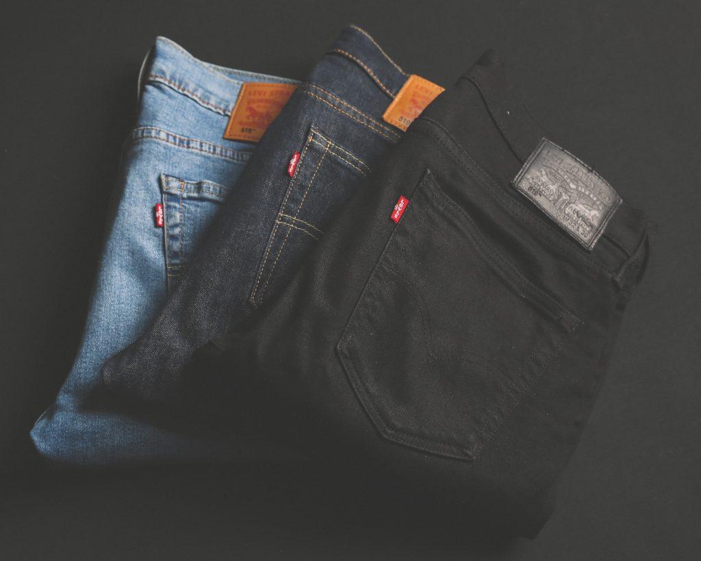 Trois paires de jeans pliées. Coloris bleu clair, bleu foncé et noir.