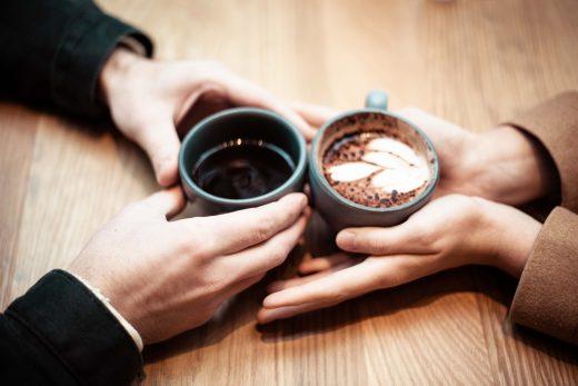 Gros plan sur les mains d'un homme et d'une femme, regroupées au milieu de la table avec des chocolats chauds