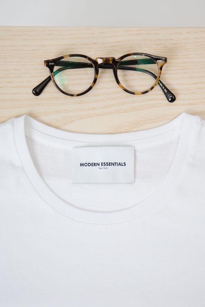 Gros plan sur un t-shirt blanc à col rond et une paire de lunettes de vue moderne