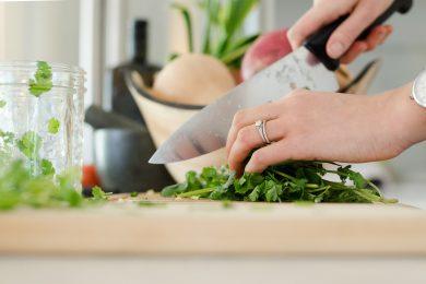zoom sur les mains d'une femme qui coupe des herbes aromatiques avec un couteau de cuisine