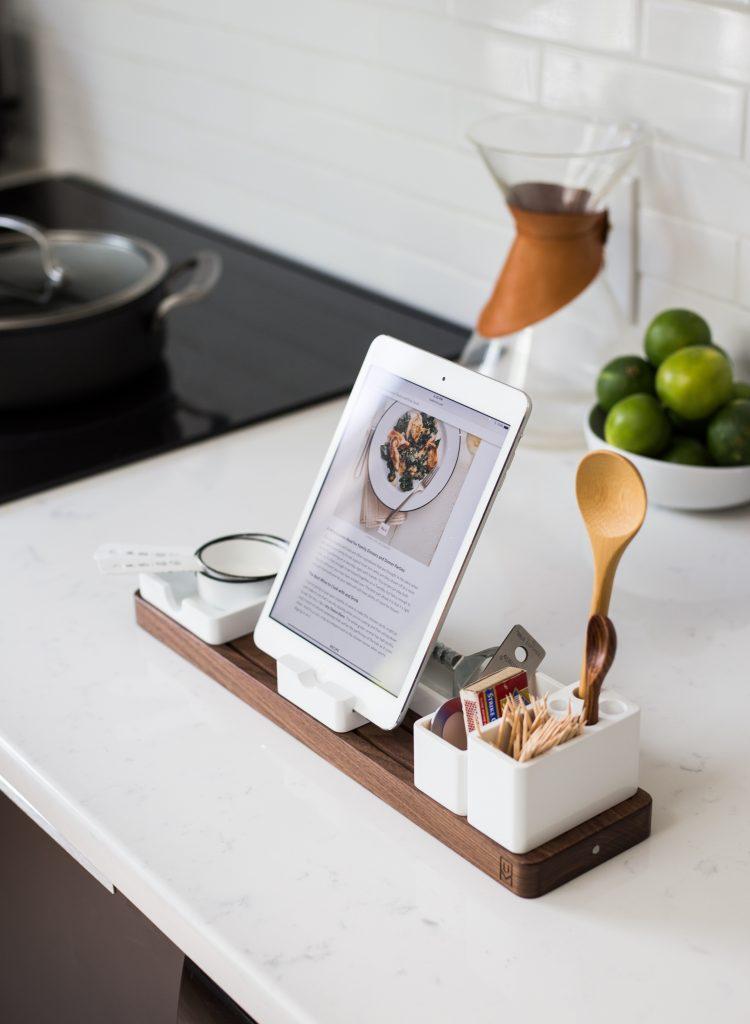 ustensiles de cuisine et tablette avec la recette sur un support en bois