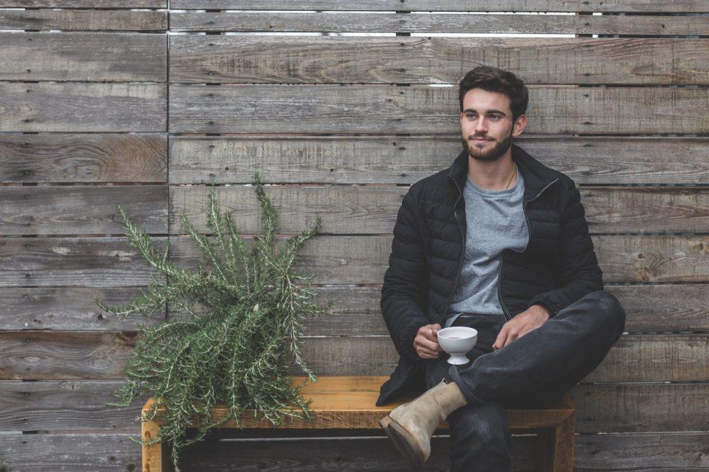 jeune homme assis sur un banc à côté d'une plante portant un t-shirt gris un jean des bottines beiges et une doudoune noire