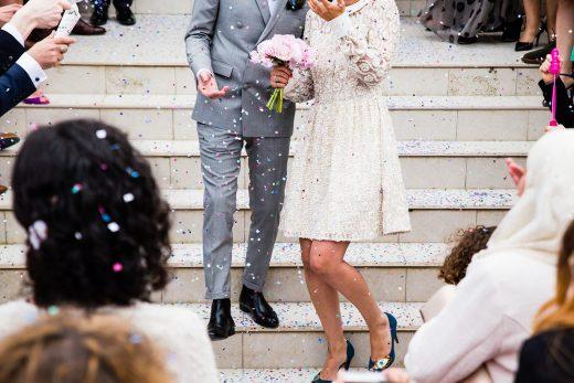 couple de mariés descendant des marches sous les cotillons