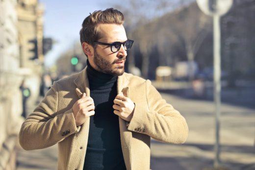homme portant des lunettes, un pull à col roulé noir et une veste beige