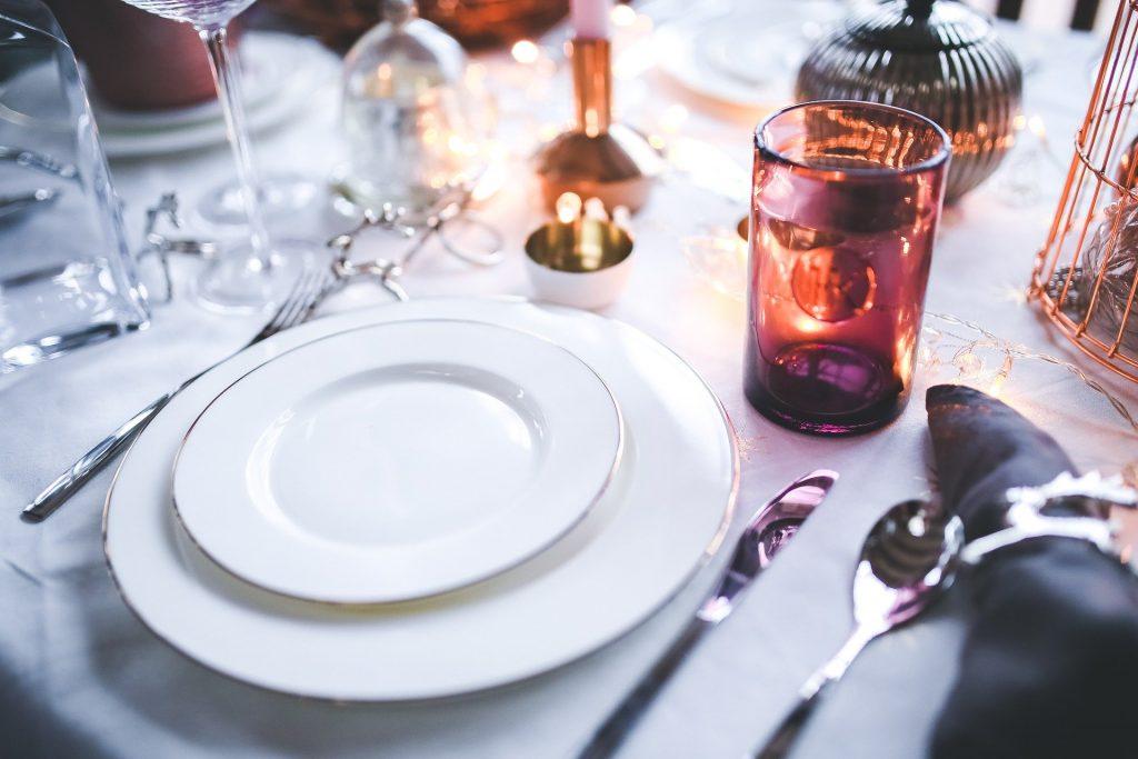 Table de Noël décorée avec des bougies, des serviettes en tissu, de la belle vaisselle blanche et des couverts en argent