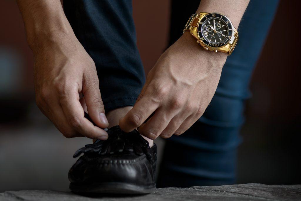 homme portant une montre dorée et un pantalon bleu marine replaçant les liens de ses mocassins noirs