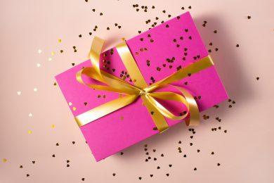 paquet cadeau avec papier rose et ruban doré et paillettes parsemées