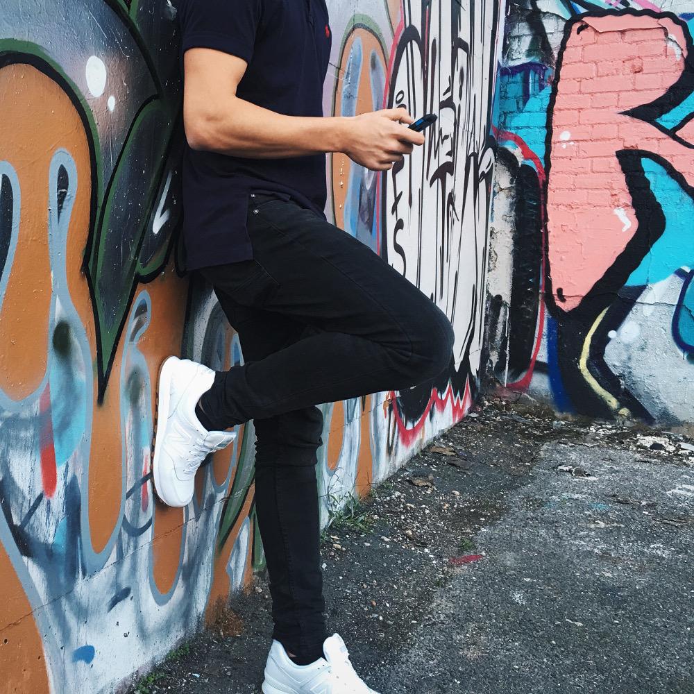 homme portant un t-shirt noir un pantalon noir et des baskets blanches