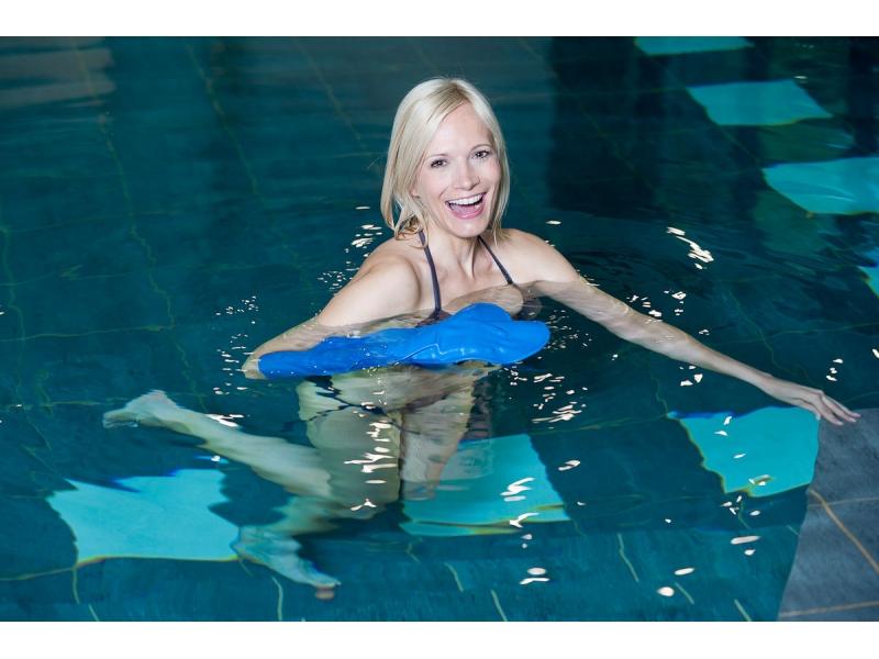 protège plâtre sur bras d'une femme blonde dans une piscine